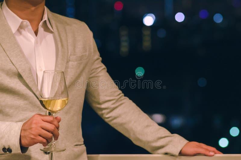 穿着灰色颜色衣服的商人站立在拿着一杯白酒的屋顶酒吧有城市bokeh黑暗的背景  库存照片