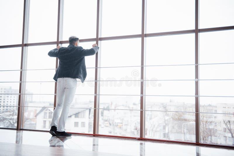 穿着现代衣服的一个时髦的年轻商人的全长射击是一位高进取者,站立在顶楼上 库存图片