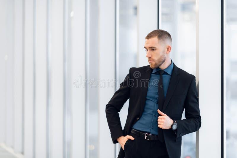 穿着现代衣服的时髦的年轻商人是一位高进取者,站立在办公楼的顶楼上 免版税库存照片