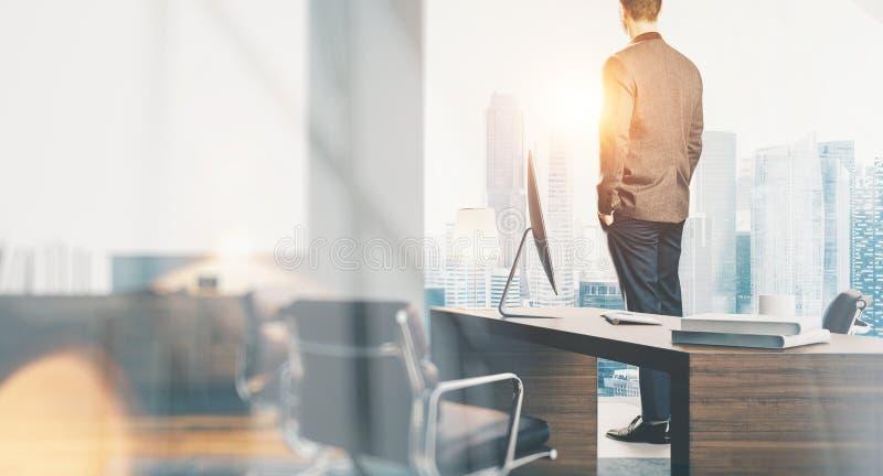 穿着现代衣服和看城市的商人在当代办公室 有全景窗口的工作区顶楼 免版税库存照片