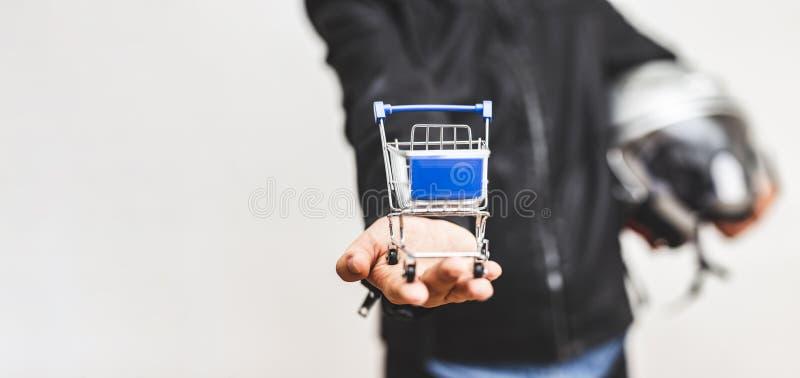 穿着皮夹克的男人手拿着小购物车 — 网上购物理念 免版税库存图片