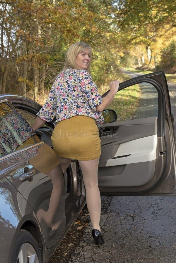 穿着短裙的妇女司机 免版税库存照片