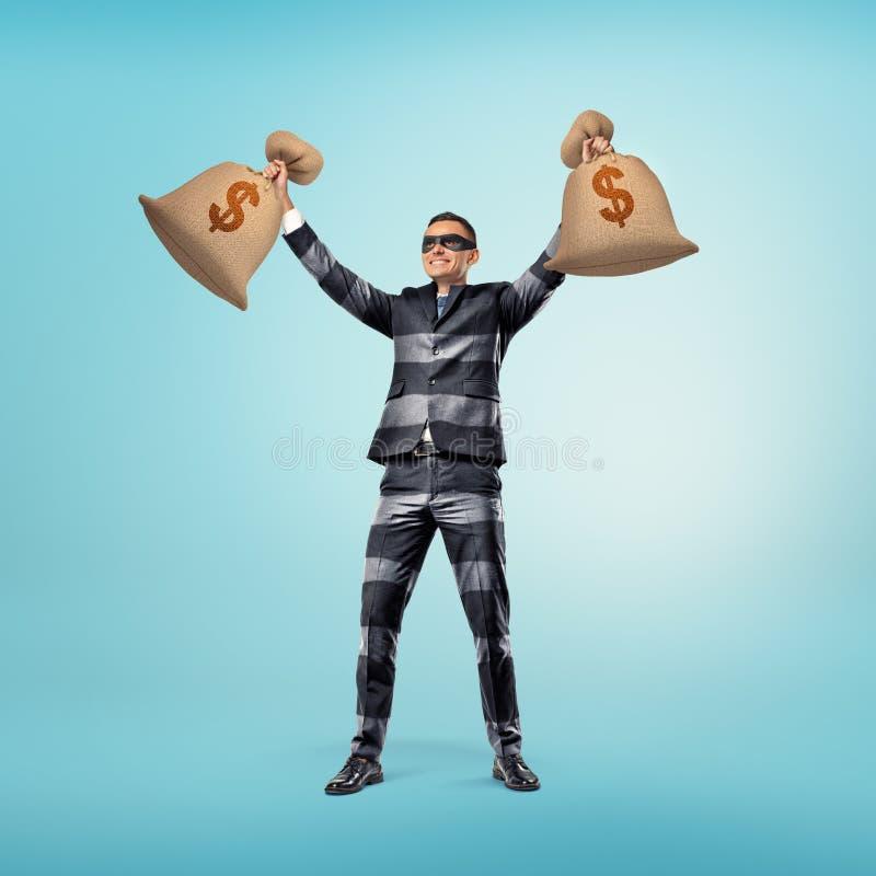 穿着类似夜贼的成套装备和黑眼圈眼罩有条纹的商人的经典衣服站立与他的 免版税库存图片