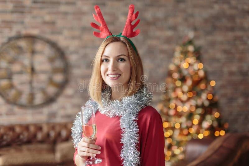 穿着红色连衣裙、在现代阁楼里喝香槟的滑稽头带的快乐年轻女人 免版税库存图片