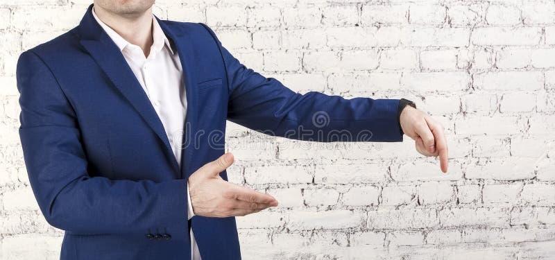 穿着经典蓝色衣服的商人指向下来 没有面孔,白色砖背景,水平的横幅 免版税库存图片