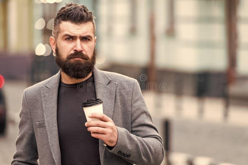 穿着考究的商人享受咖啡休息室外都市背景 周道,但是轻松 走并且享用新鲜热 库存照片