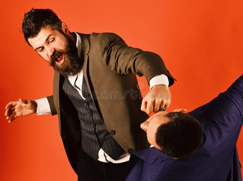 穿着聪明的衣服的商人猛击或击中同事 免版税库存图片