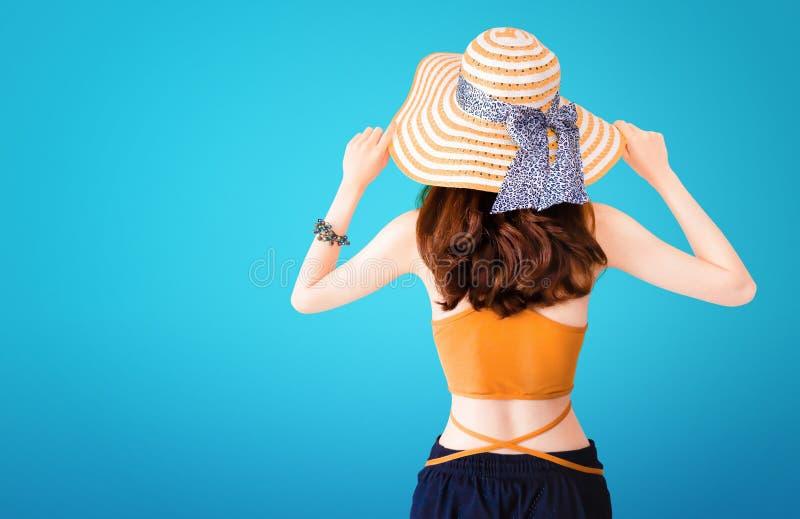 穿着草帽和性感的衣服在蓝色背景的美丽的俏丽的妇女与夏天概念 库存图片