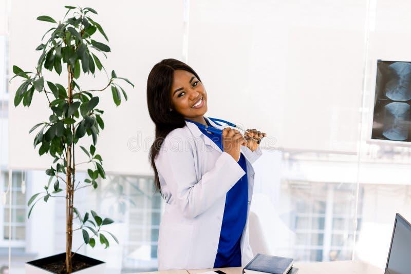 穿着蓝色医疗服和白色大衣、微笑着摆姿势自信的非洲裔美国女医生画像 免版税库存图片
