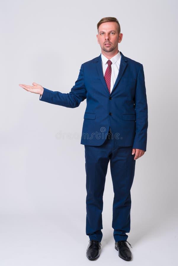 穿着蓝色衣服的白肤金发的商人充分的身体射击 免版税库存图片