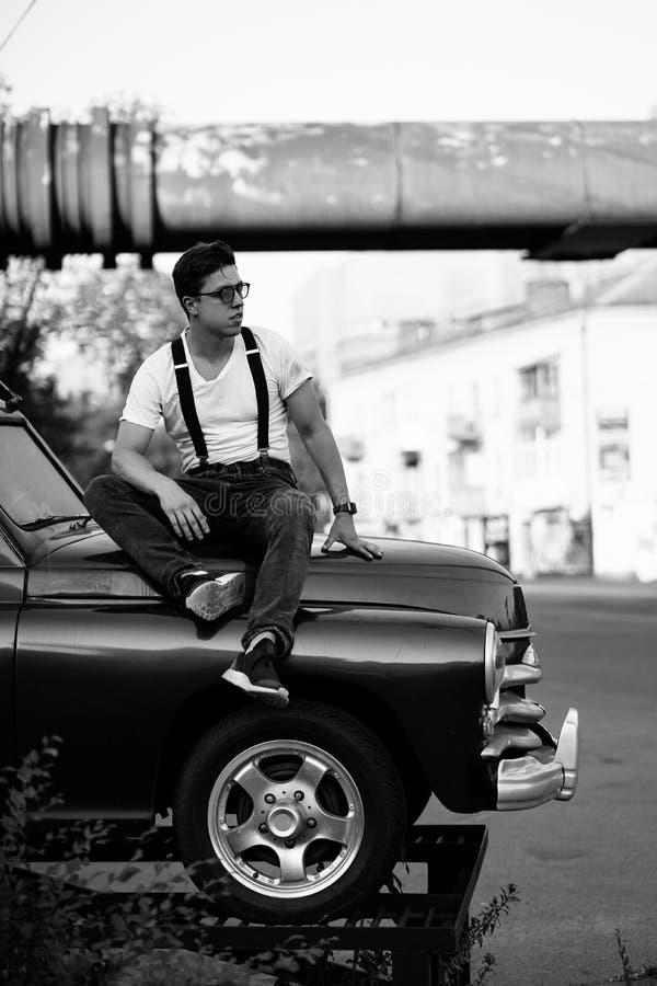 穿着衬衫的男人,在复古车前摆姿势 免版税库存照片