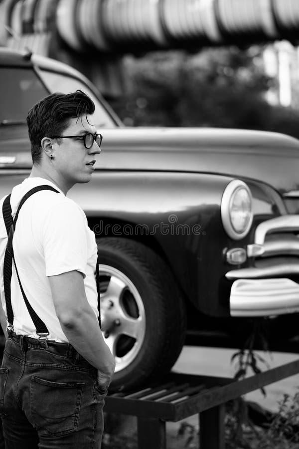 穿着衬衫的男人,在复古车前摆姿势 免版税图库摄影