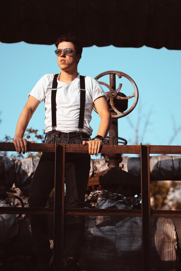 穿着衬衫的男人,在旧管道和阀门上摆姿势 库存图片