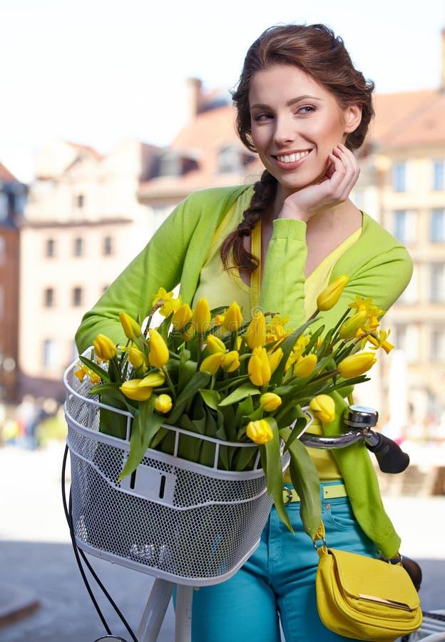 穿着象葡萄酒画报的妇女春天裙子拿着自行车 免版税库存图片