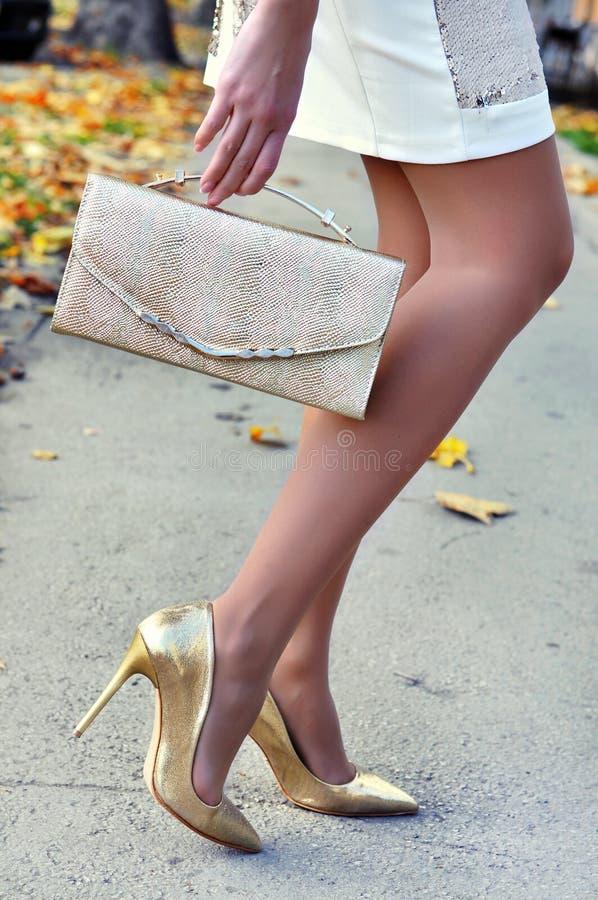 穿着金黄高跟鞋和裙子的性感的亭亭玉立的妇女腿拿着典雅的提包 图库摄影