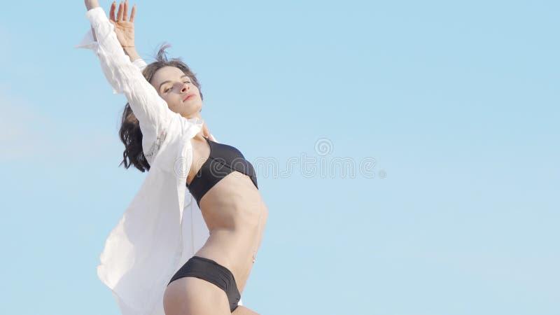 穿着黑色比基尼和白色衬衫在户外跳舞的漂亮柔软女人 免版税库存照片