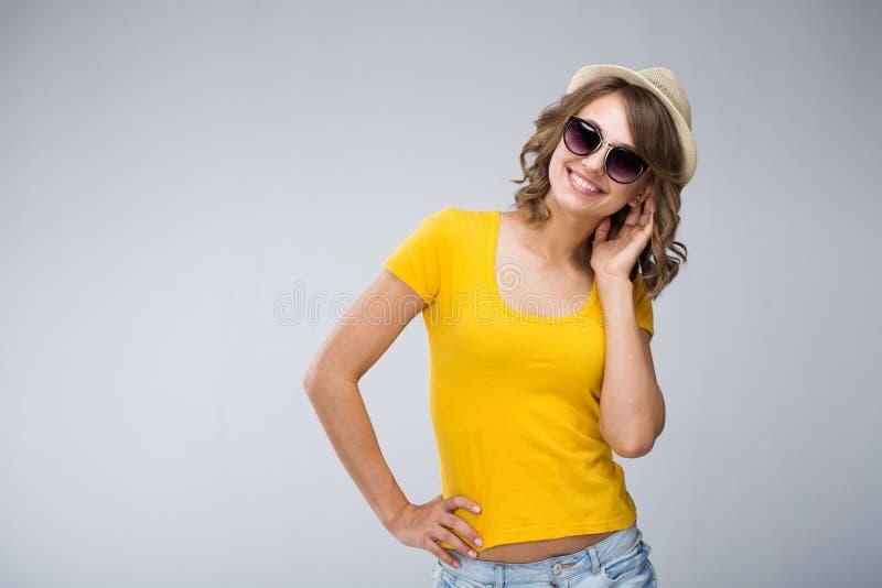 穿着黄色衬衣帽子和牛仔裤短裤的少妇做面孔 图库摄影