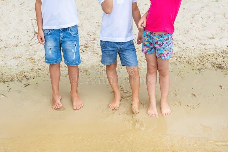 穿着casaual牛仔布短裤的小组孩子获得站立在沙子的乐趣在海滩 使用在的三个小孩朋友 库存照片