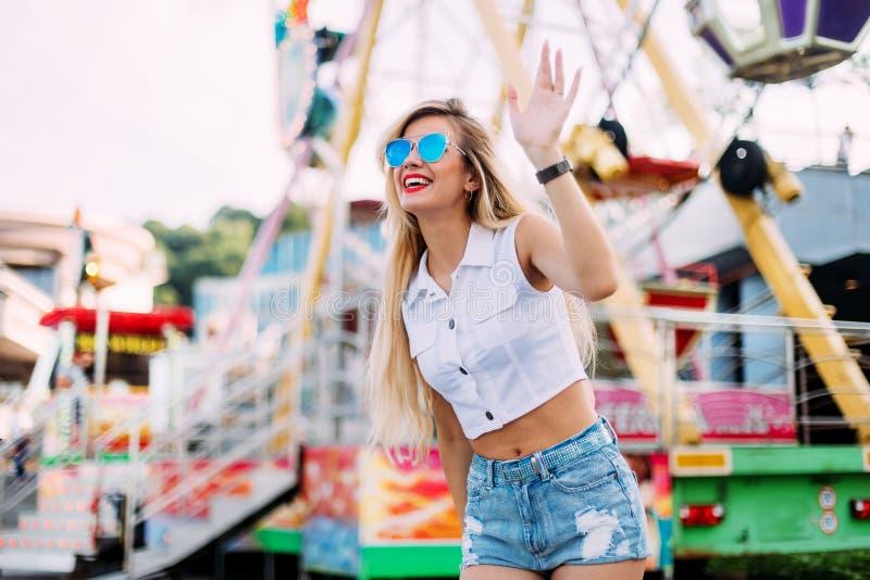 穿短的牛仔布短裤和一件白色T恤杉的时髦的愉快的少妇 brightred嘴唇 女孩纵向微笑的太阳镜 图库摄影
