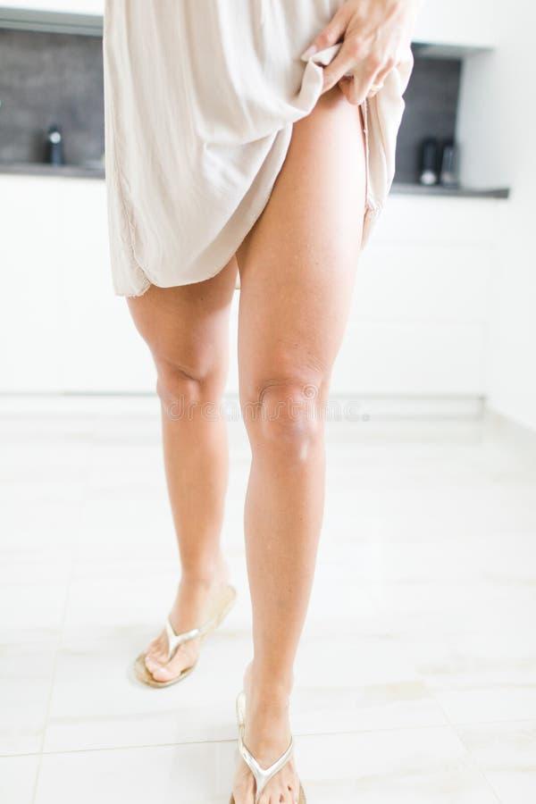 穿短的礼服的妇女显示她的锻炼腿 免版税库存照片