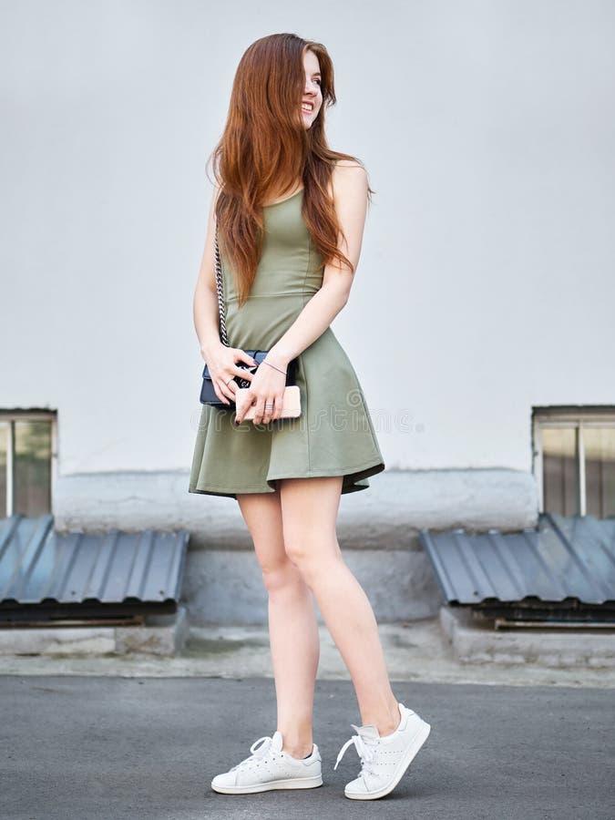 穿短的绿色礼服的年轻美丽的长的头发红头发人妇女全长画象,拿着摆在aga的手机和袋子 库存图片