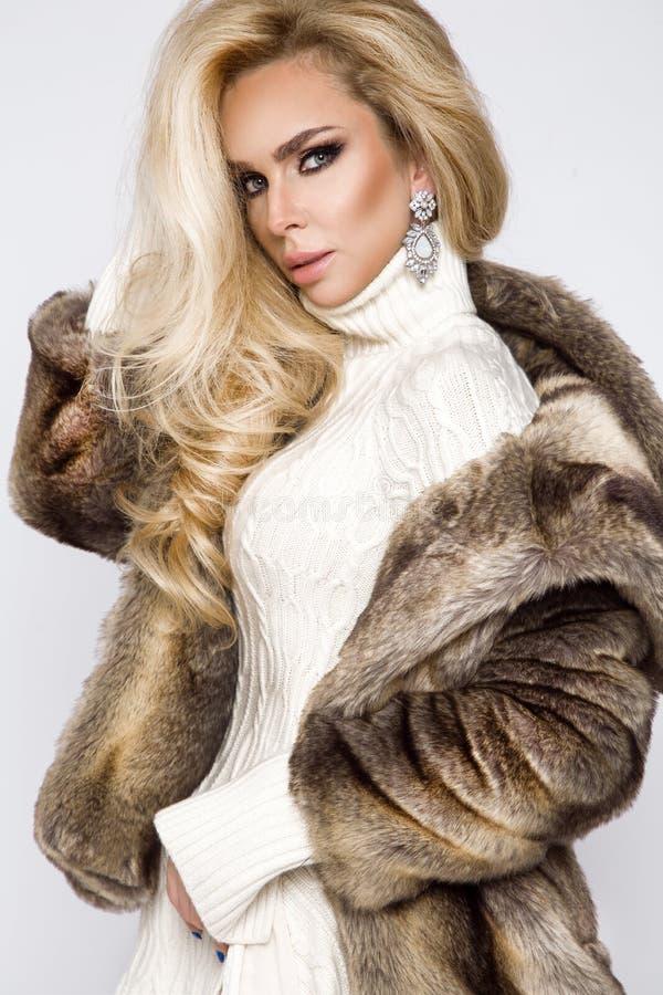 穿礼服和典雅的皮大衣的美好,性感的白肤金发的模型 免版税库存图片