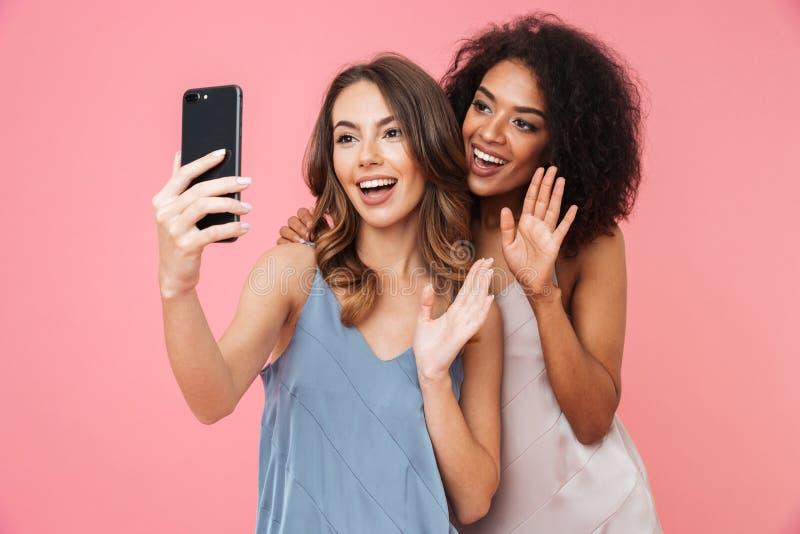 穿礼服的两个不同种族的深色的女孩假期照片  免版税图库摄影