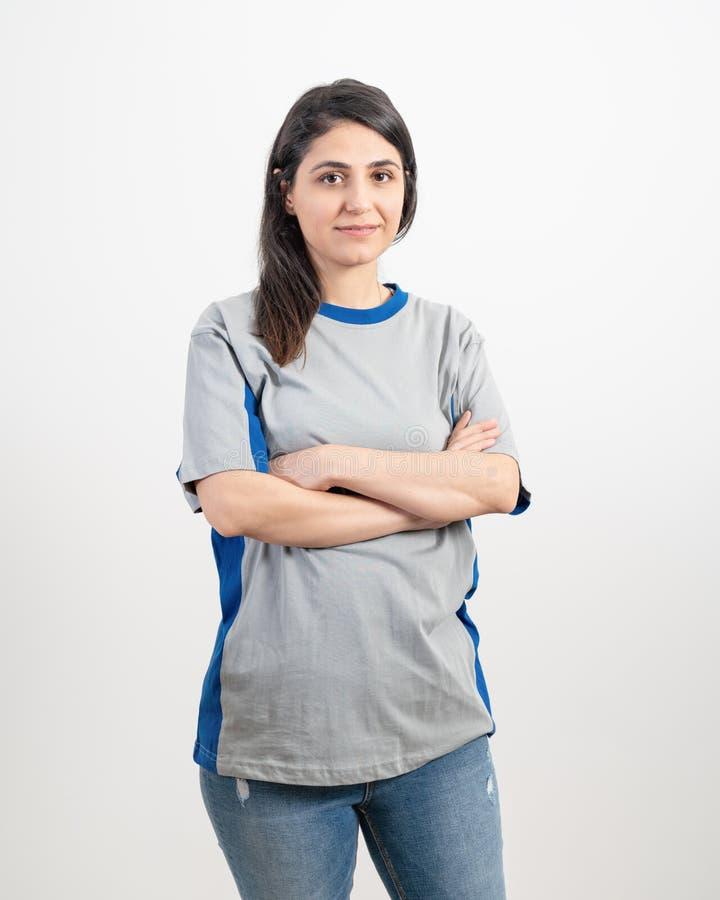 穿空白的灰色T恤杉和蓝色牛仔裤的少女 灰色墙壁背景 库存照片