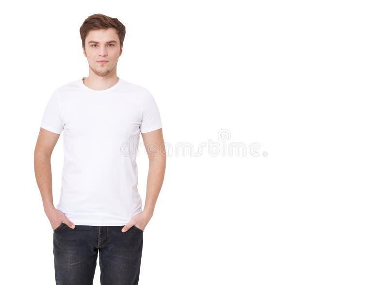 穿空白的白色T恤杉的年轻人隔绝在白色背景 复制空间 T恤杉的地方广告的 图库摄影