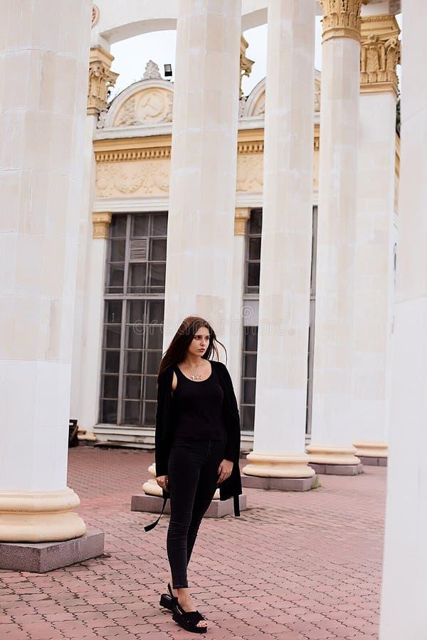 穿空白的黑T恤杉、牛仔裤和外套的女孩生活方式画象摆在反对与专栏的大厦 免版税库存照片