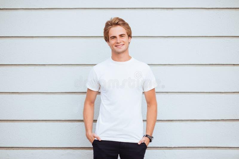 穿空白的T恤杉和蓝色牛仔裤的年轻人 库存图片