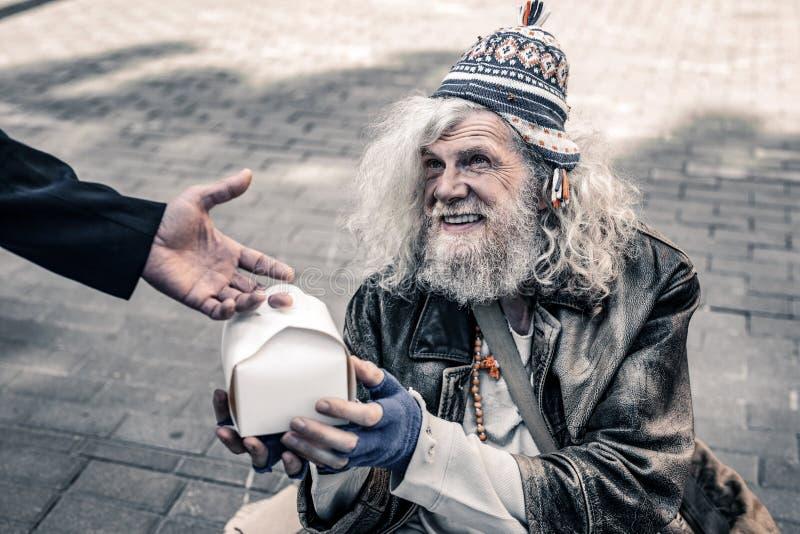 穿穿破的服装和接受食物的肮脏的灰发的资深无家可归者 库存图片