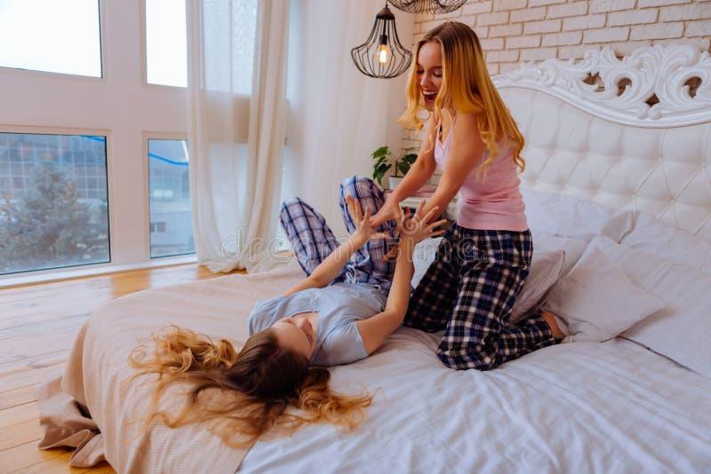穿精密睡衣的两个姐妹获得乐趣在卧室 免版税库存图片