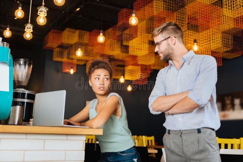 穿精密衬衣的金发的上司观看他的雇员 免版税库存照片