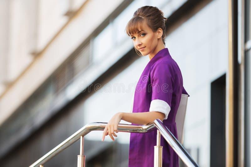 穿紫色燃烧物的年轻时装业妇女走在城市街道 库存照片