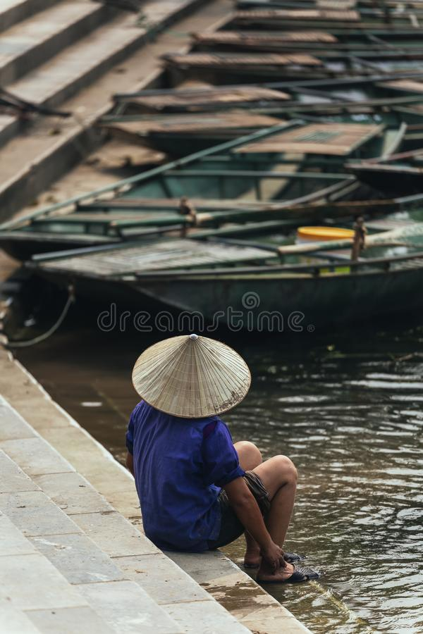 穿紫色衬衣的妇女,圆锥形帽子在有空的划艇的河运载洗涤她的脚在背景中 库存图片