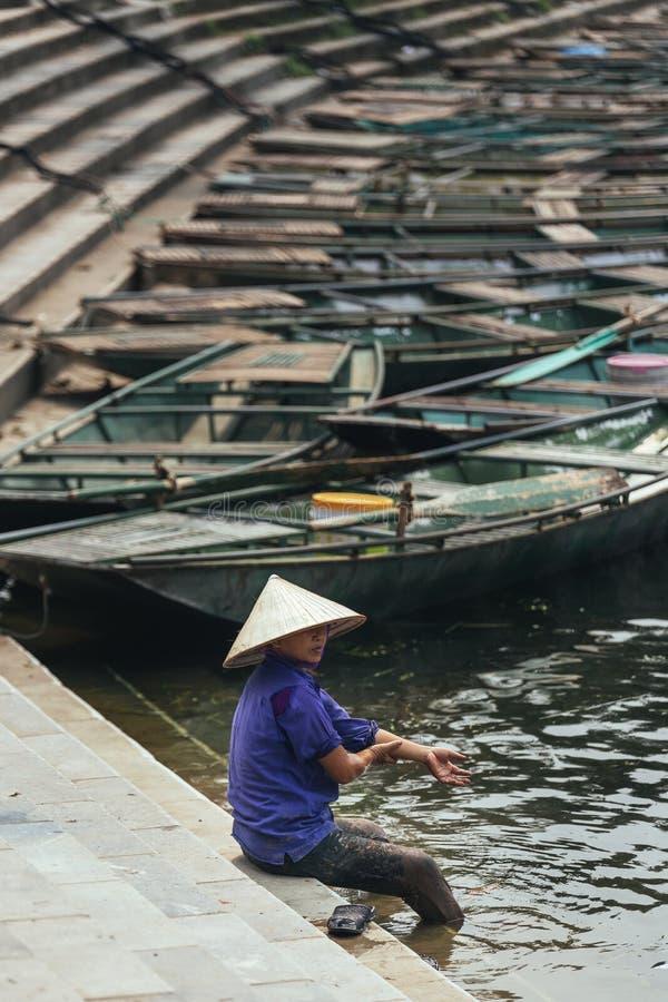 穿紫色衬衣的妇女,圆锥形帽子在的Trang运载洗涤她的脚在有空的划艇的河在背景中 库存图片