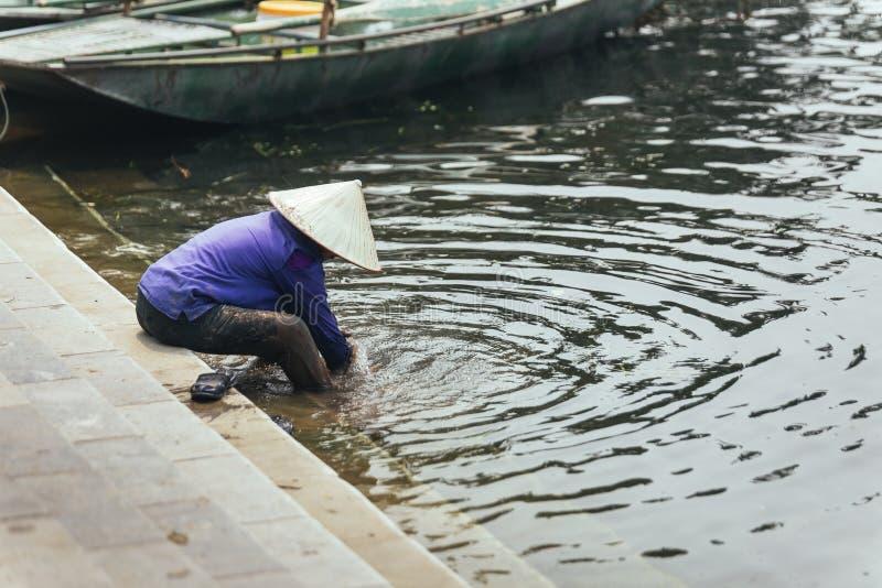 穿紫色衬衣的妇女,圆锥形帽子在的Trang运载洗涤她的脚在河洞穴在Ninh Binh,越南 库存照片