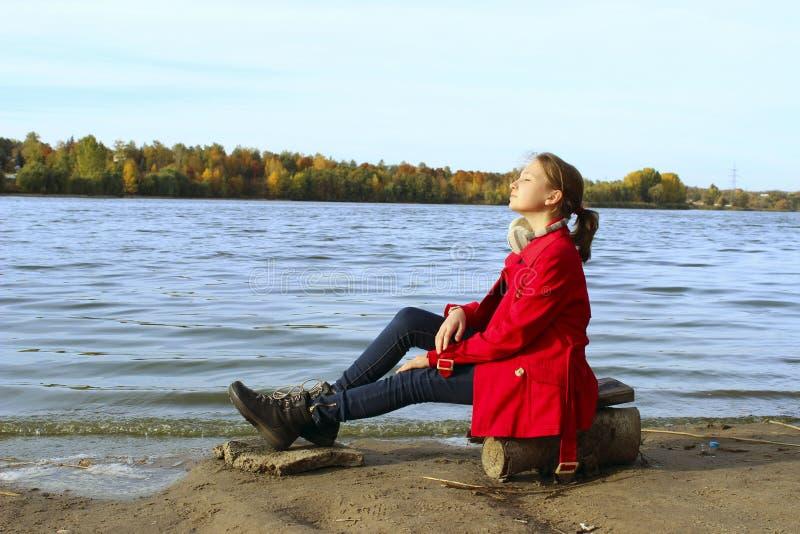 穿红色外套和蓝色牛仔裤的少女放松户外 青春期前的女孩 免版税库存照片