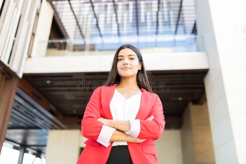 穿红色夹克的愉快的女性经理 免版税库存照片