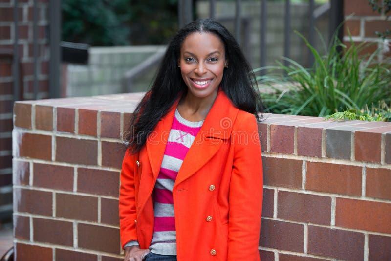 穿红色夹克的愉快的美丽的非裔美国人的妇女站立和微笑在学生学院校园 免版税图库摄影