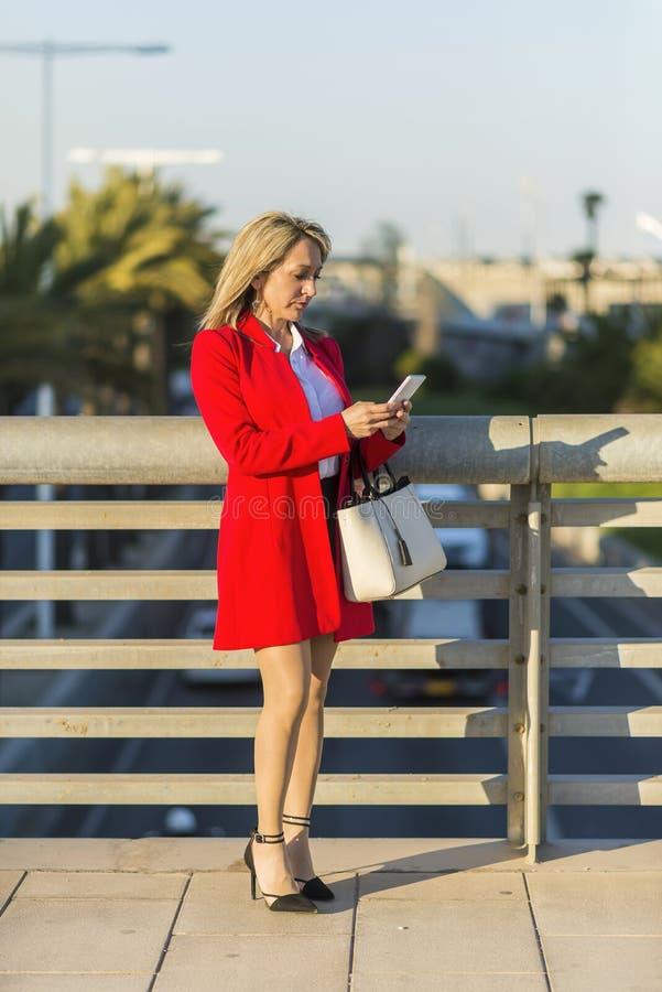 穿红色夹克的白肤金发的妇女使用在st的一个电话身分 免版税库存照片