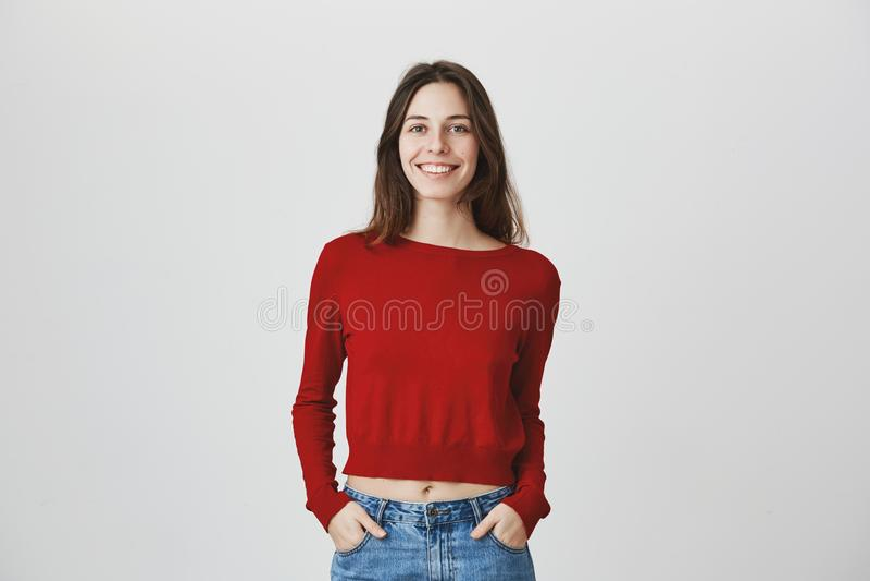 穿红色套头衫和牛仔布牛仔裤的年轻悦目女性白种人学生画象微笑,握手  免版税库存照片