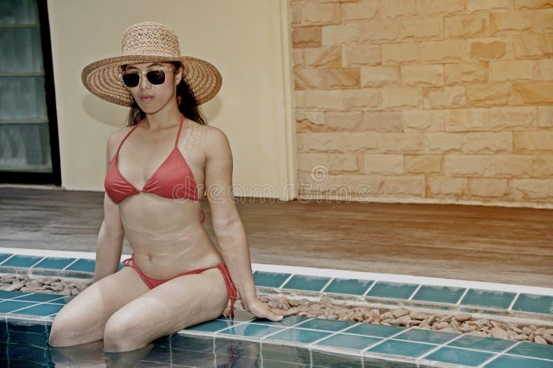 穿红色比基尼泳装的俏丽的亚裔妇女坐在与草帽和太阳镜的游泳场边缘 免版税库存图片