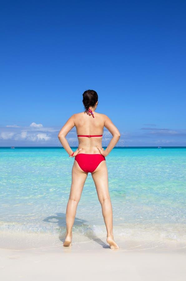 穿红色比基尼泳装的年轻亚裔妇女 免版税库存照片