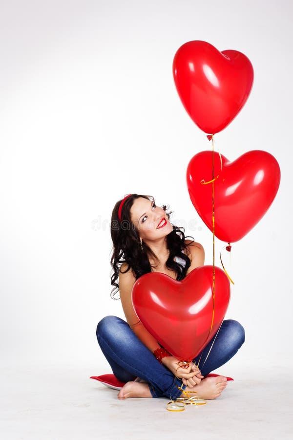 穿红色礼服和拿着红色气球的情人节美丽的少妇 免版税库存照片