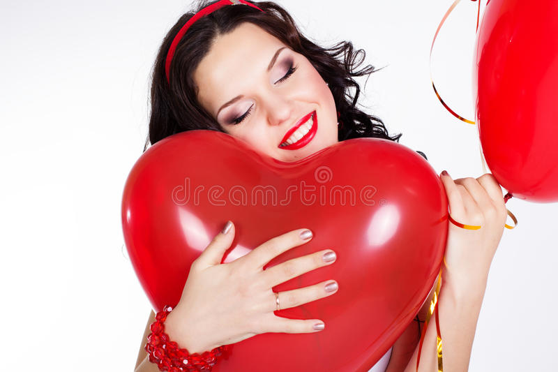 穿红色礼服和拿着红色气球的情人节美丽的少妇 免版税库存图片
