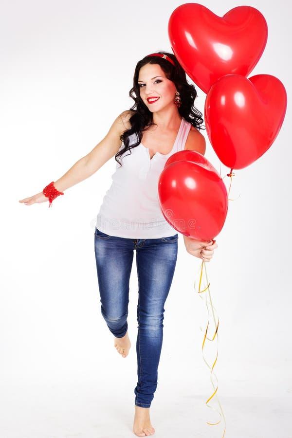穿红色礼服和拿着红色气球的情人节美丽的少妇 库存照片