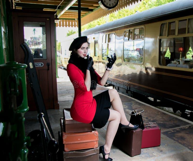 穿红色礼服和黑贝雷帽的葡萄酒可爱的女性,坐申请她的构成的手提箱在火车站 免版税库存照片