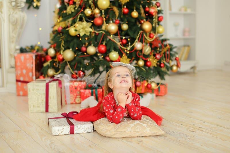 穿红色礼服的小女孩说谎在圣诞树和礼物附近 库存照片
